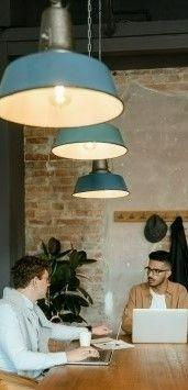 На фото изображен офис где два человека обсуждают деловое предложение