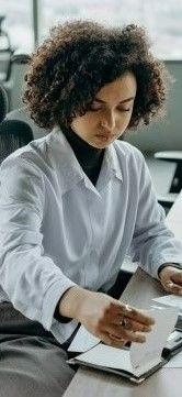 На фото девушка в офисе работает за ноутбуком