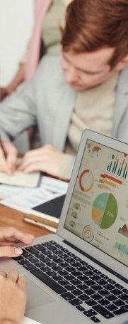 Фото, где показан офис с ноутбуком показывающий графики и мужчину который пишет в блокнот