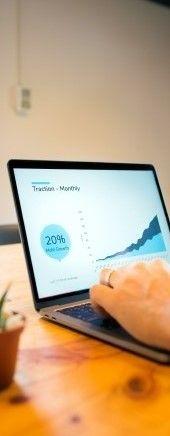 На фото мужчина смотрит график на ноутбуке