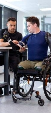 На фото доктор помогающий пациенту лучше адаптироваться к протезам
