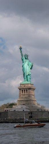 На фото изображена лодка где на фоне стоит статуя свободы