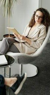На фото комната, где девушка сидит на стуле и ведет беседу