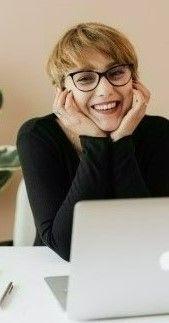На фото девушка сидит у себя в комнате и работает на ноутбуке