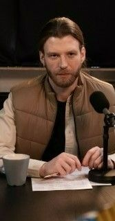 На фото мужчина сидит на стуле в комнате и разговаривает по микрофону