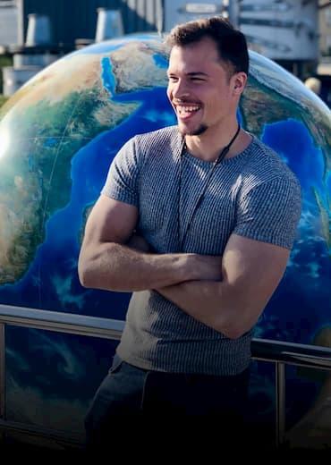 На фото молодой человек смеётся на фоне глобуса