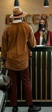 На фото мужчина стоит на ресепшене и бронирует себе место в отеле