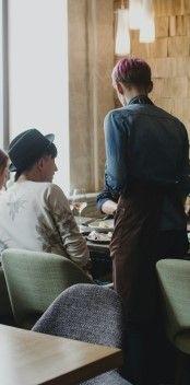 На фото изображено кафе, где официант принимает заказ у клиента