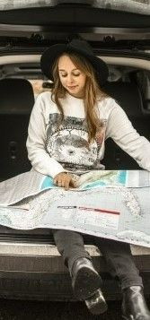 На фото девушка рассматривает карту сидя на багажнике