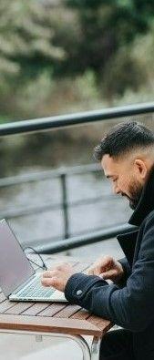 Фото мужчина общается через ноутбук сидящий на улице напротив реки