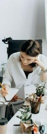 На фото девушка в комнате сидит на стуле и записывает данные в документ