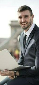На фото молодой человек сидит на улице с ноутбуком