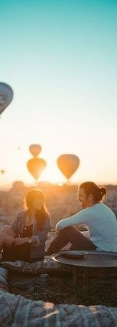 На фото мужчина с девушкой разговаривают и смеяться на фоне воздушных шаров