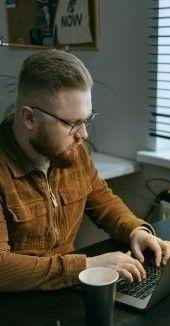 На фото мужчина работает через ноутбук у себя в комнате