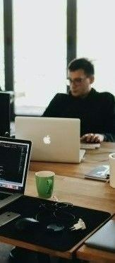 На фото парень работает на ноутбуке в офисе