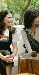 На фото две девушки сидящие в уличном кафе и обсуждая интересные ситуации