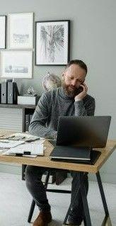 На картинке мужчина работает на ноутбуке у себя дома