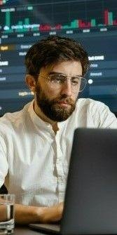 На картинке молодой человек работает за ноутбуком
