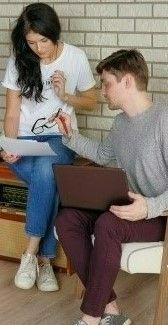На фото девушка с парнем обсуждают распечатанный документ