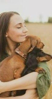 На фото девушка держит на руках собачку на фоне поля