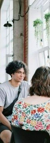На фото мужчина с девушкой сидят в кафе и разговаривают