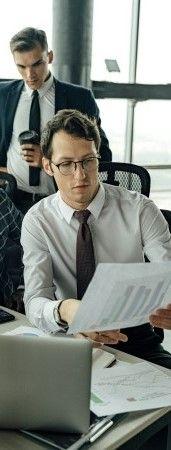 На фото мужчина распечатал документ с графиками и показывает другому парню