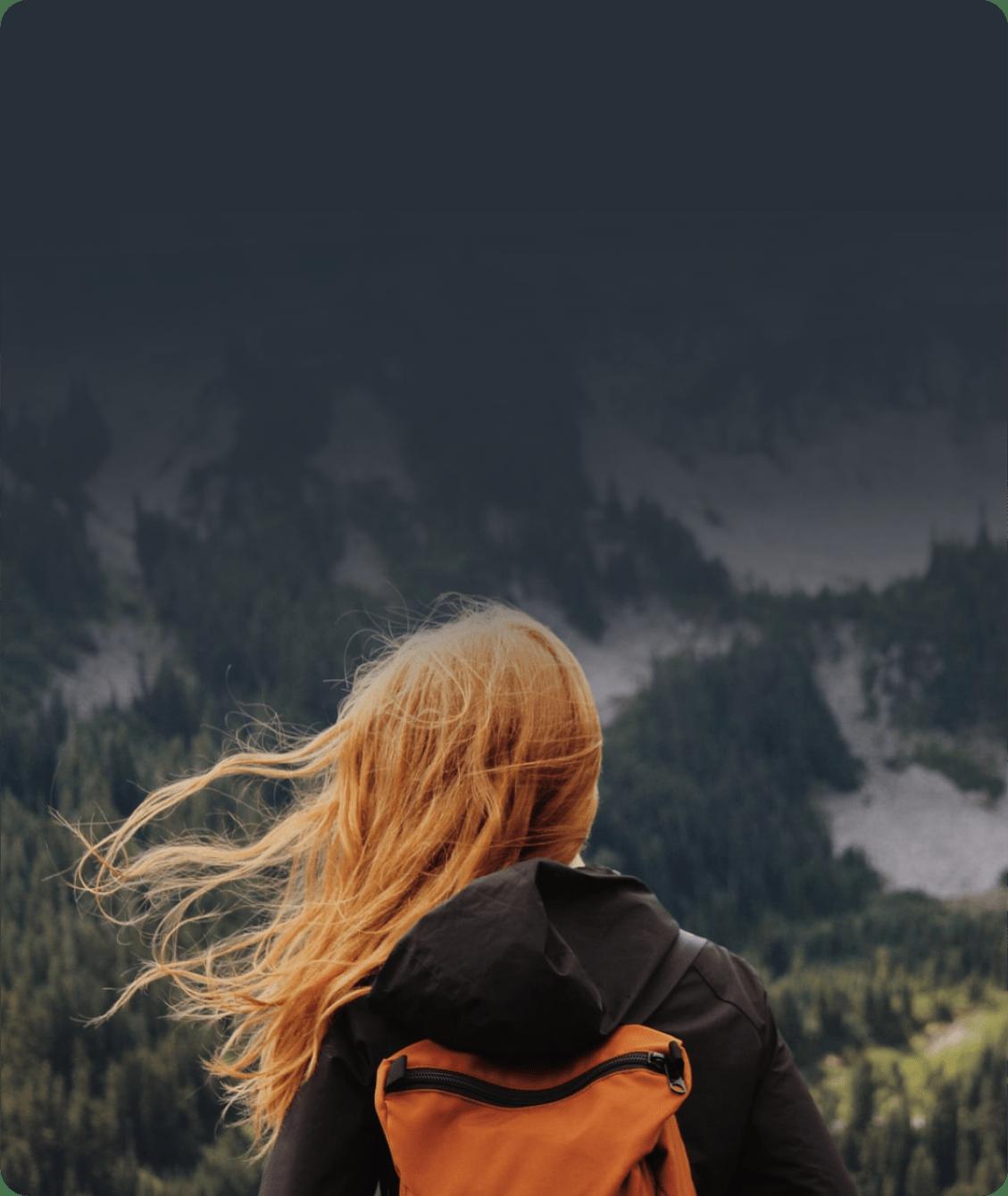 На фото девушка стоит на фоне горы