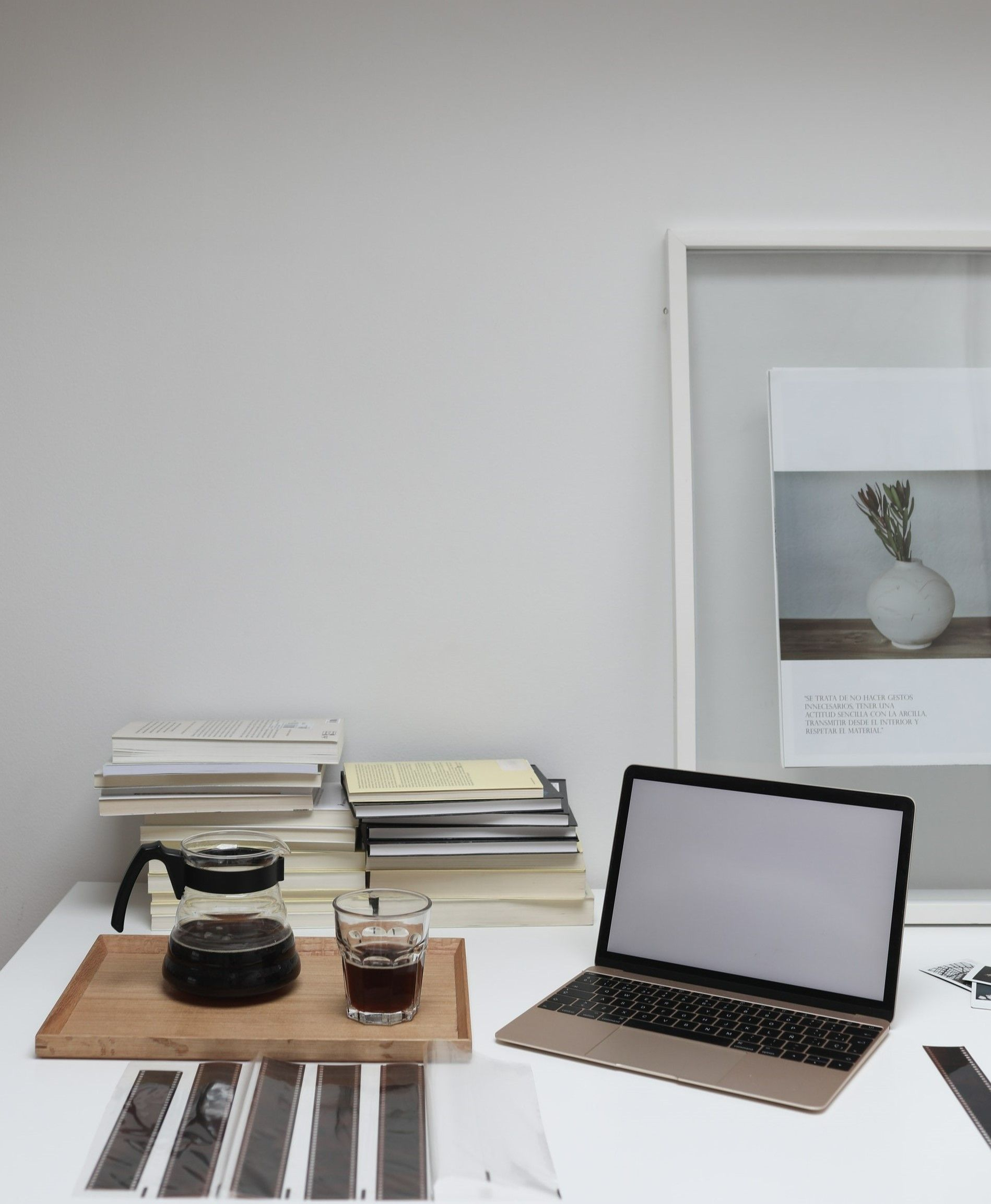 На фото офис со столом на котором лежит ноутбук, книги, документы и стакан с кофе