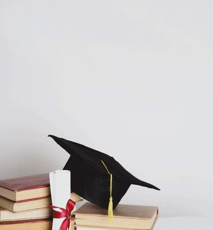 Картинка с серым фоном на которой стоит стол с книгами и с шапкой-конфедераткой четырехугольной формы