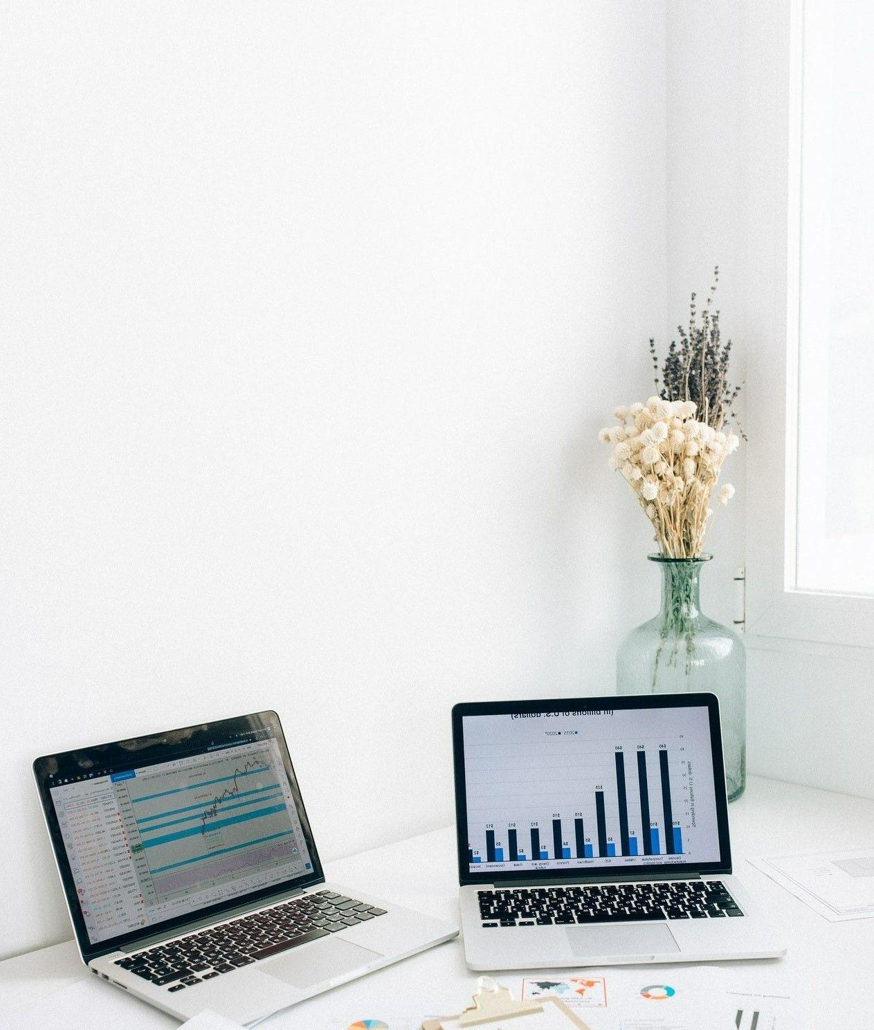 Картинка где в офисе на столе лежат два ноутбука с изображением графиков на мониторе