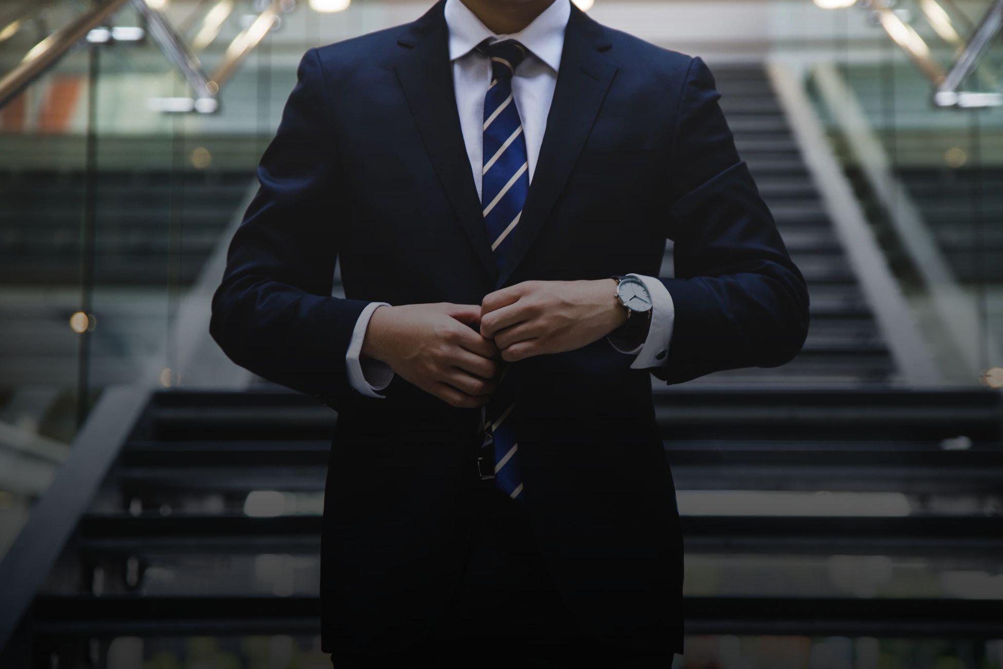 Фото с мужчиной в костюме который застегивает пуговицу