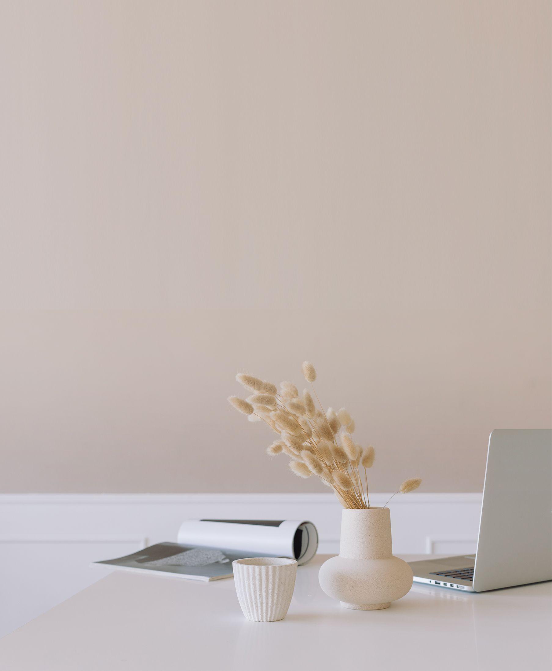 На фото изображен стол на котором лежит ноутбук, ваза, чашка и журнал
