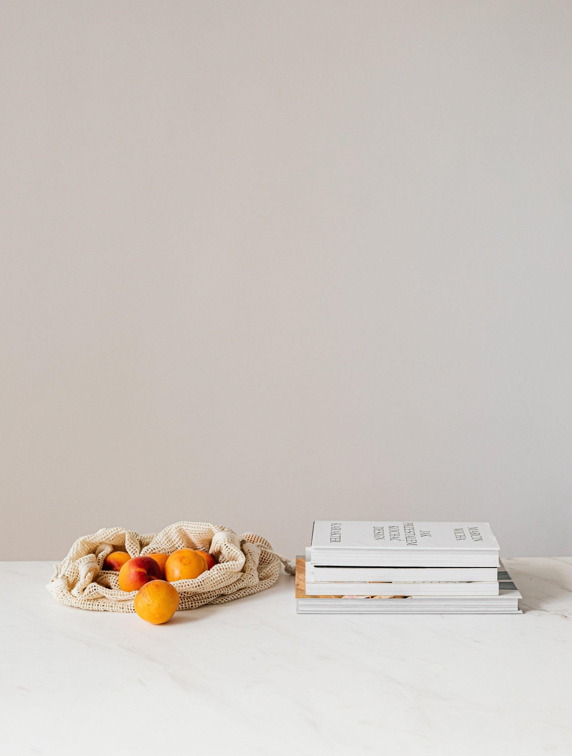 На картинке с бежевым фоном стоит стол на котором лежит связка апельсинов и книги