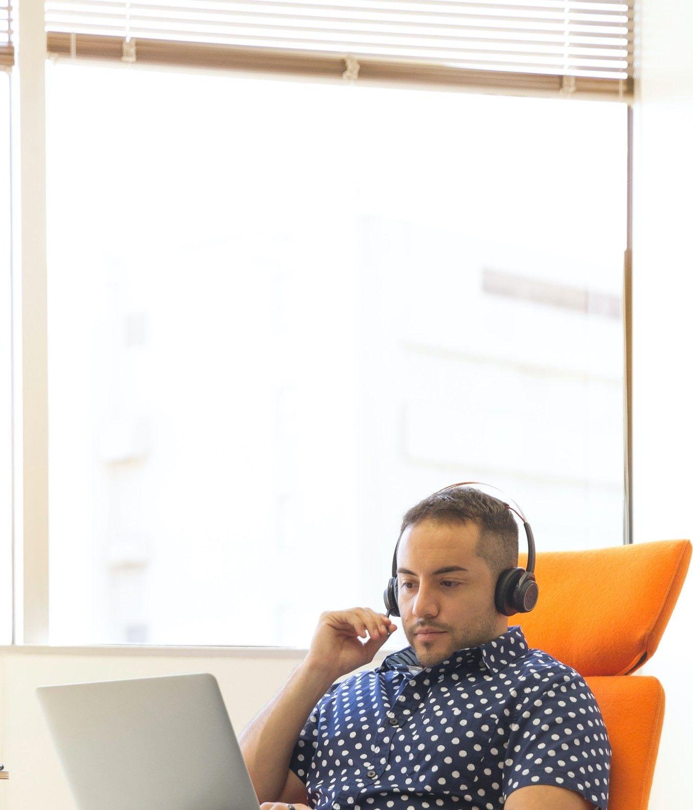 На фото изображен мужчина в комнате общающийся через ноутбук