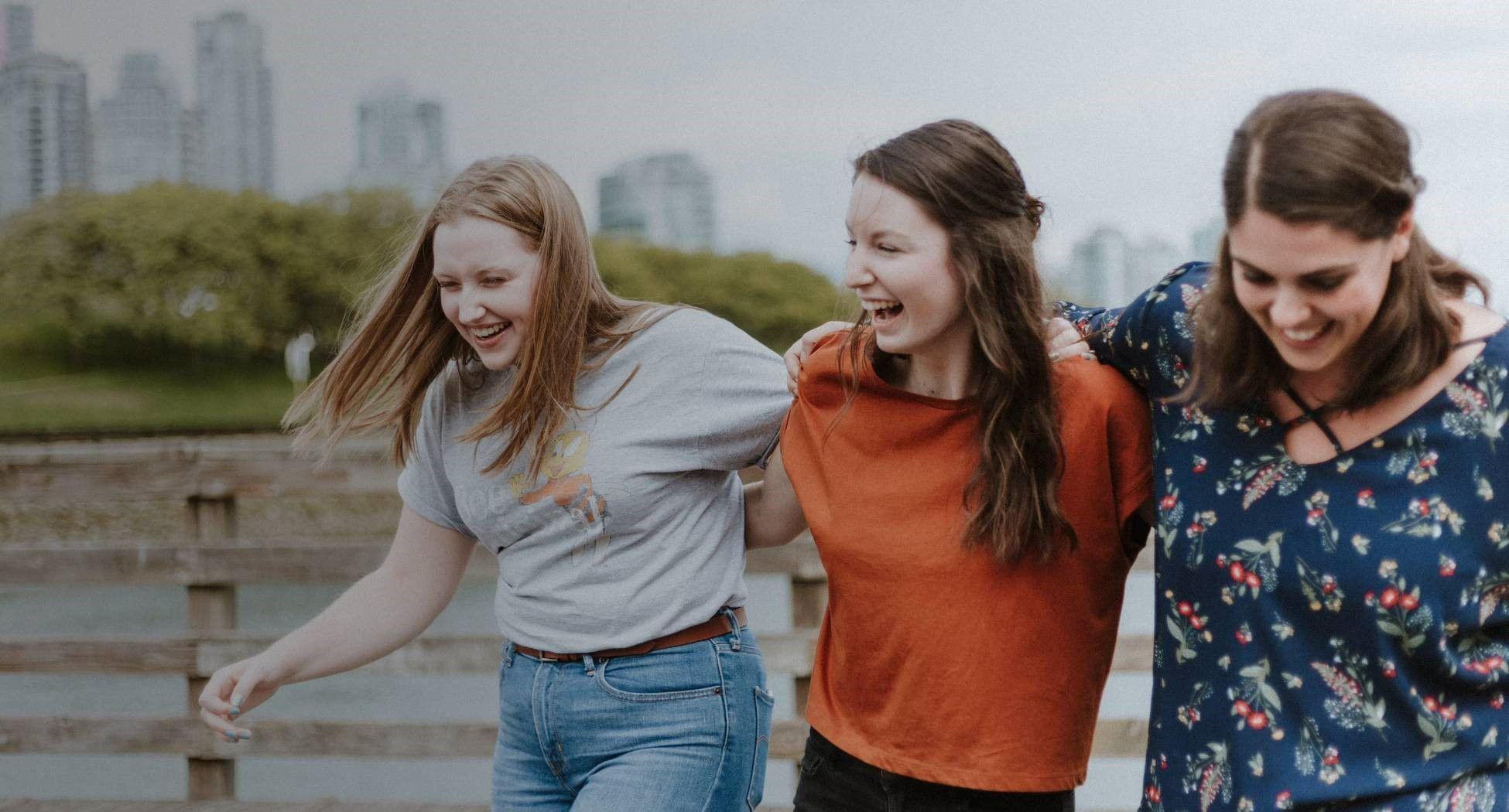 На фото трое девушек гуляют по улице и смеются