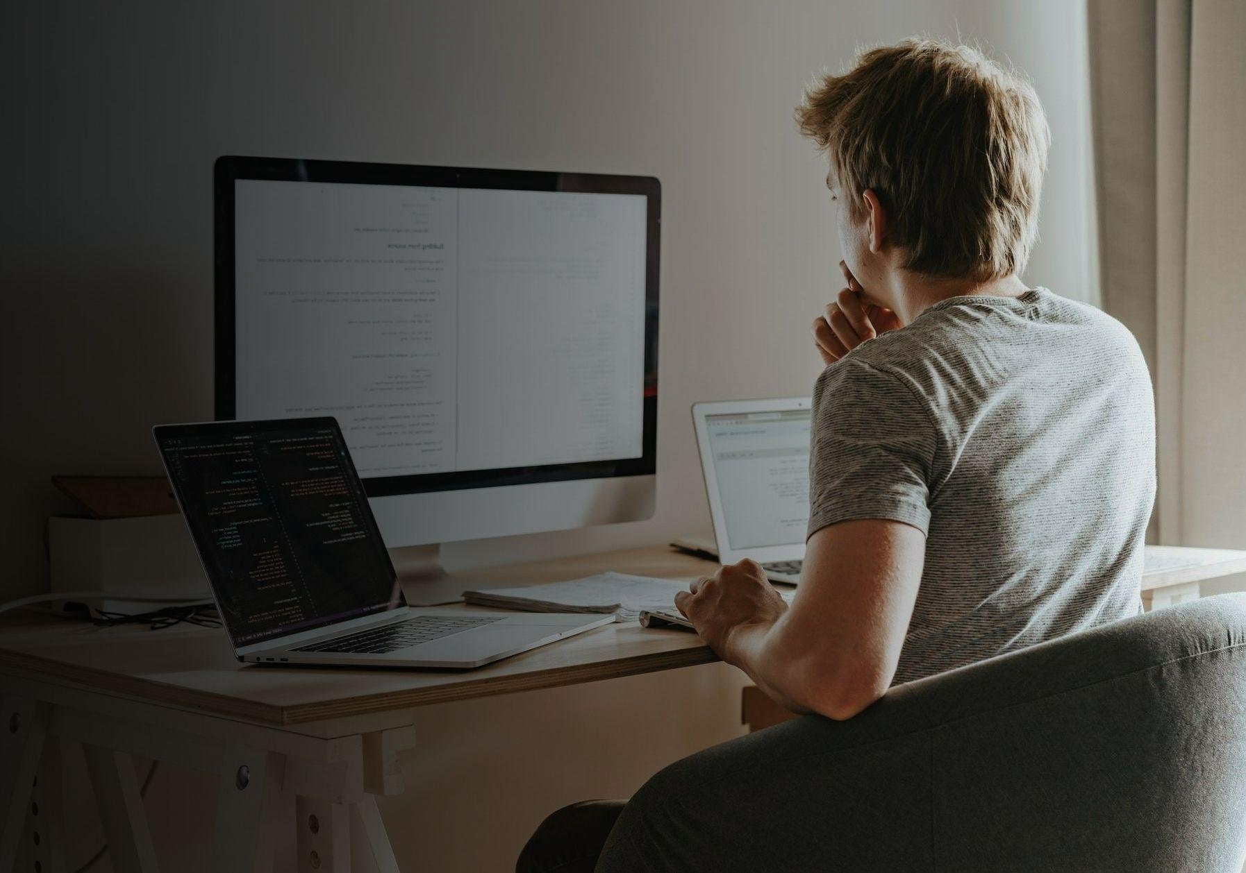 Фото с мужчиной сидящий на стуле перед компьютером