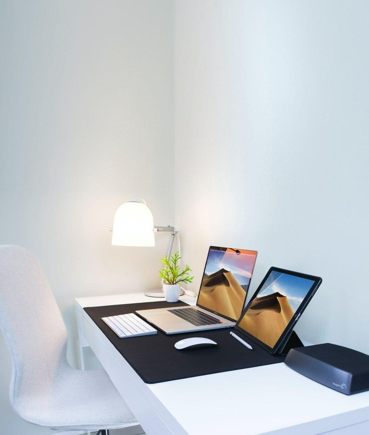 На картинке офис со столом на котором лежат два ноутбука