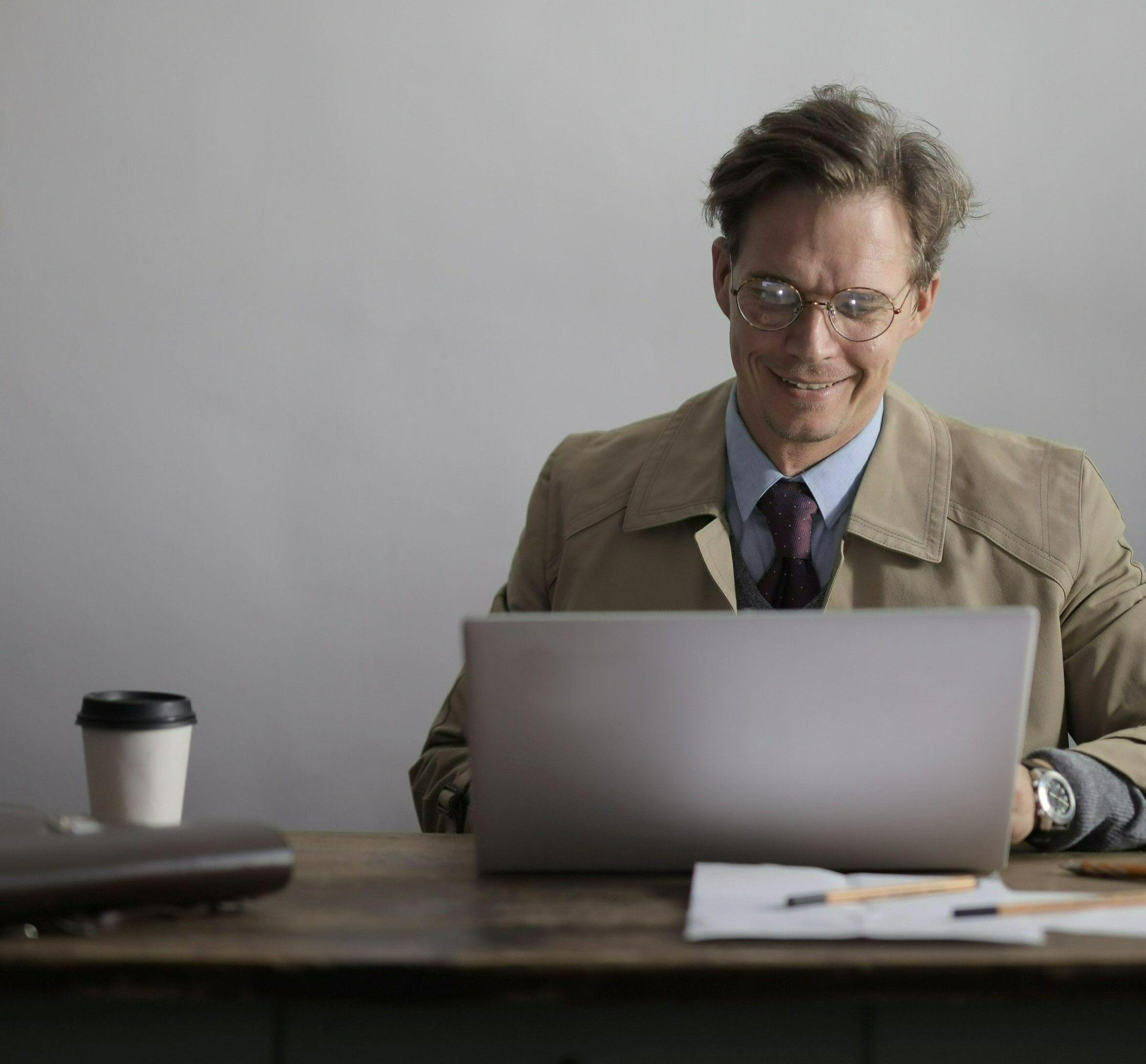 Фото с мужчиной в комнате сидящий на диване перед ноутбуком