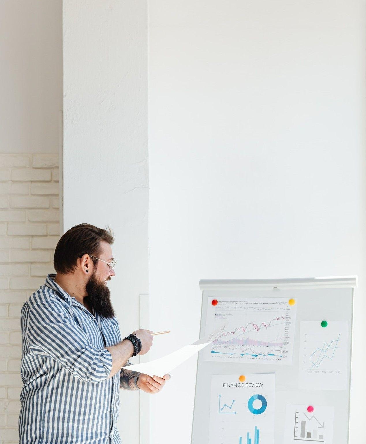 На фото, где мужчина находясь в офисе показывает отчетность о проделанной работе на доске