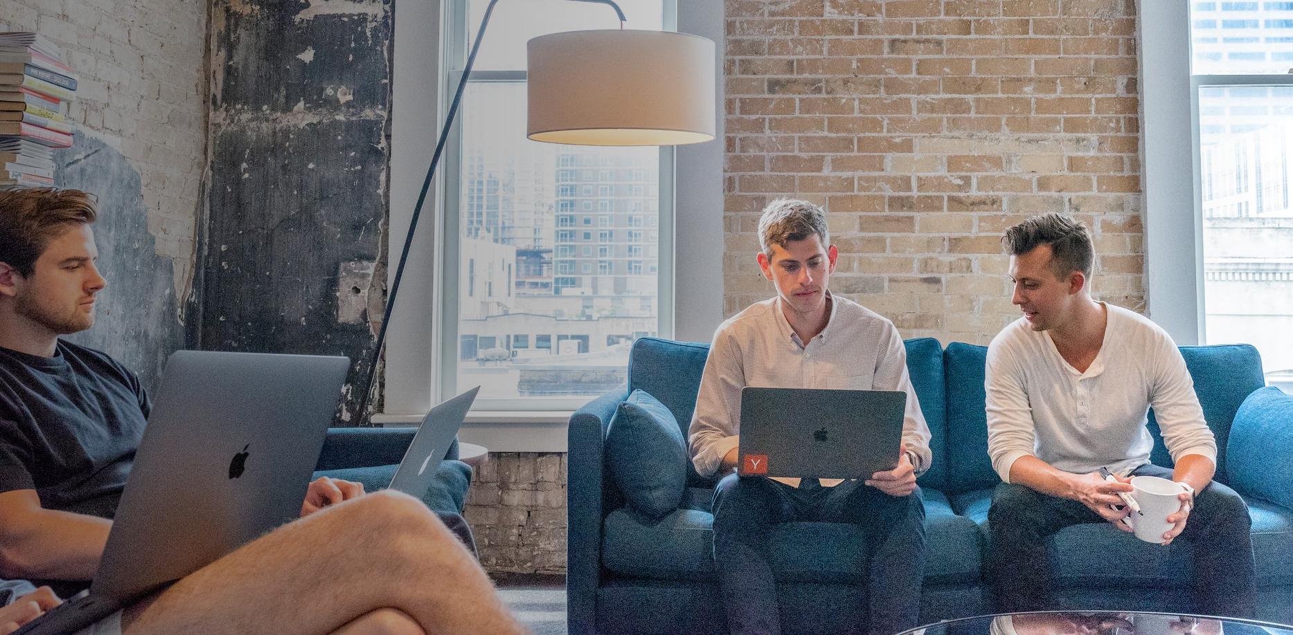 Фото с двумя мужчинами сидящие в комнате перед ноутбуком и разговаривают