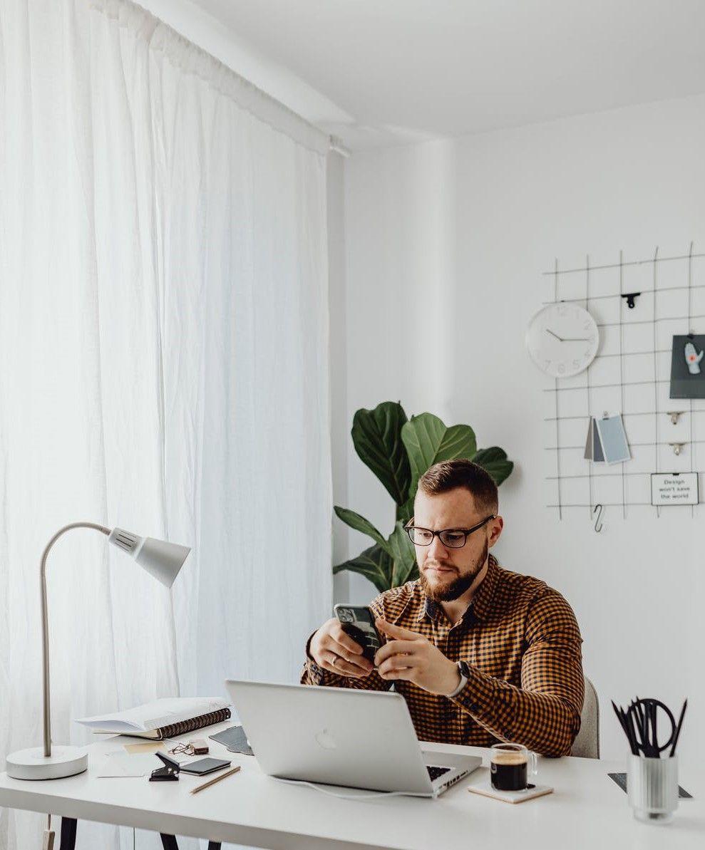 На фото мужчина сидит в офисе за ноутбуком и общается через мессенджер на телефоне