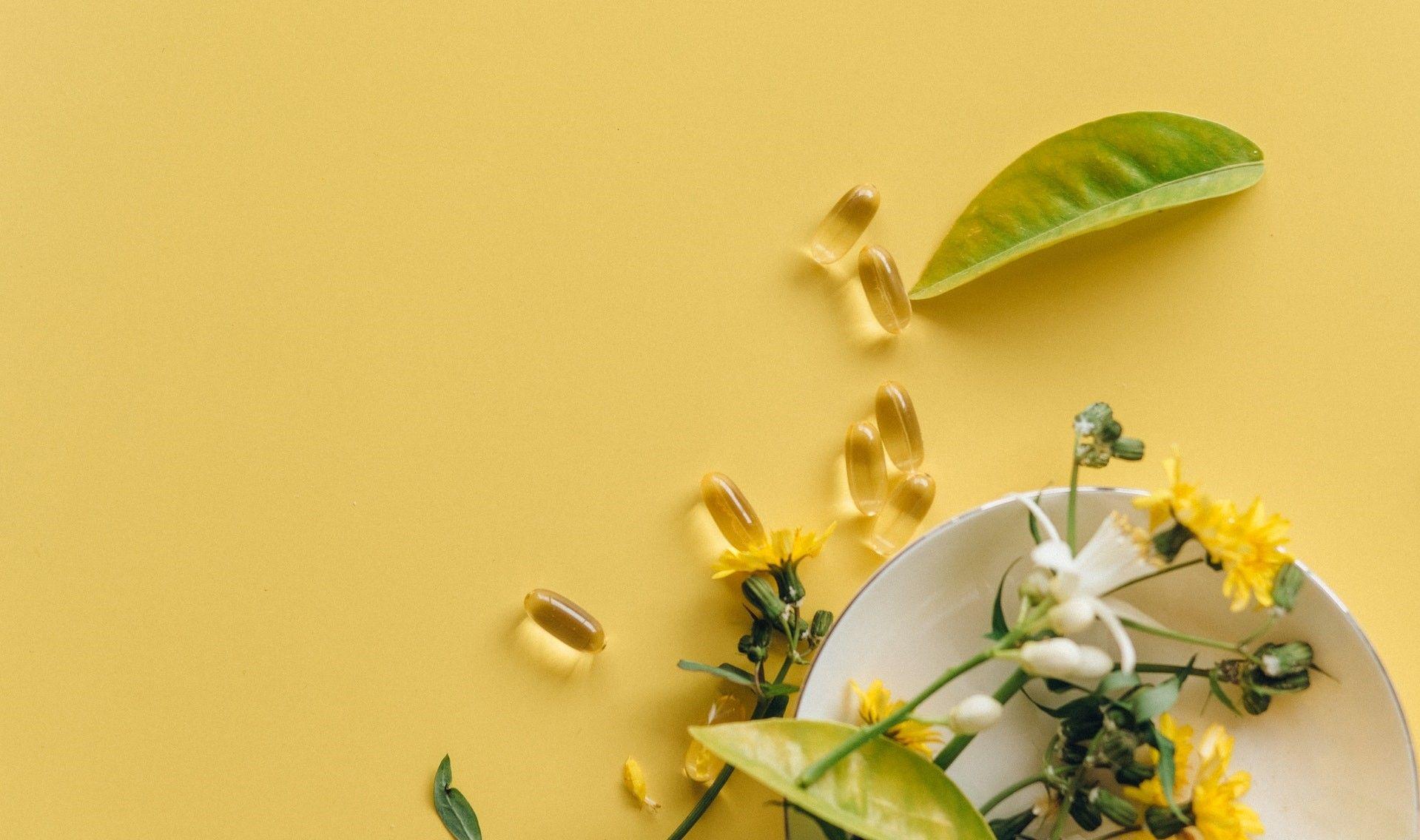 Изображение с желтым фоном на котором лежит листочек и капсула лекарства