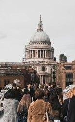 Фото, где люди гуляют по улице города на фоне собора