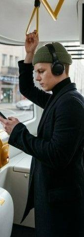 На картинке парень в троллейбусе изучает английский язык через телефон и наушники
