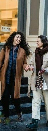 На фото две девушки идущие с покупками и разговаривающие на английском языке