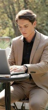 Фото, где молодой человек сидит в уличном кафе и учит через ноутбук английский язык