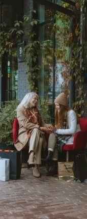 На фото две девушки сидят на улице и разговаривают на английском языке