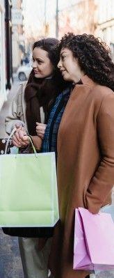 На фото две девушки рассматривают витрину магазина