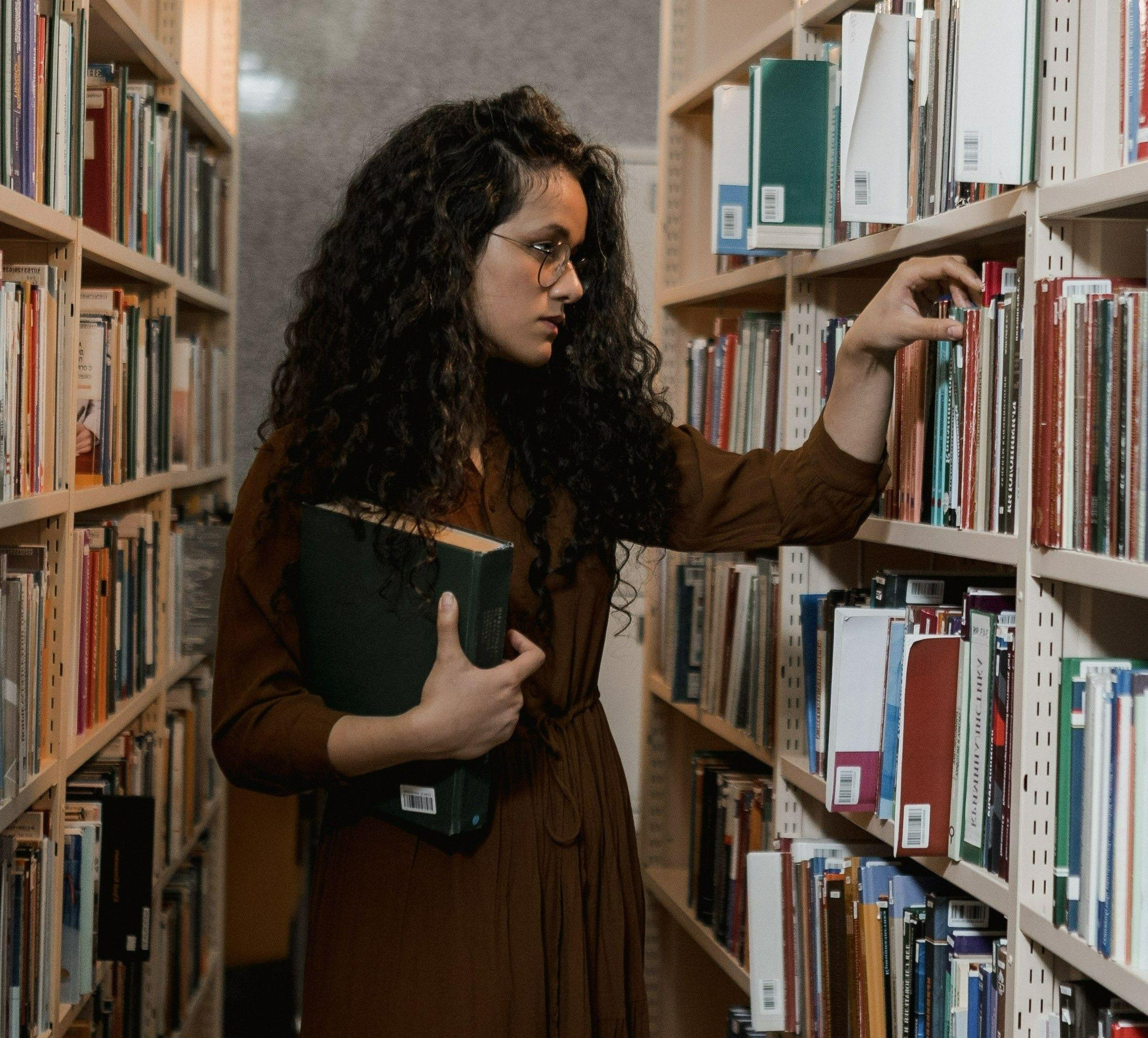Фото с девушкой в библиотеке ищущею книгу на английском языке
