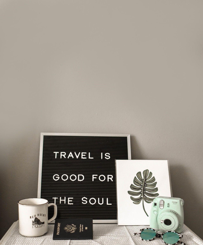 На фото изображен стол на котором стоит табличка с надписью о путешествие, кружка, паспорт, фотоаппарат, очки и картина с листочком
